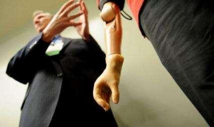Todd Kuiken (L) explains the bionic arm on Glen Lehman