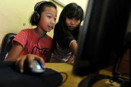 Two Indonesian girls surf the web an Internet shop in Jakarta