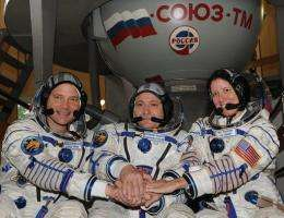 US astronaut Doug Wheelock (L), Russian cosmonaut Fyodor Yurchikhin (C), and US astronaut Shannon Walker (R)