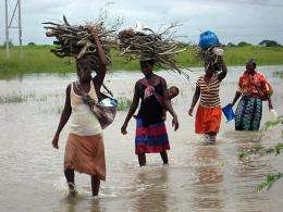 Women wade through water covering the street near the Limpopo river, Mozambique, in January