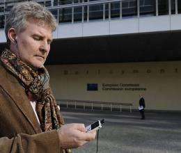 A man listens to an mp3 player through his earphones