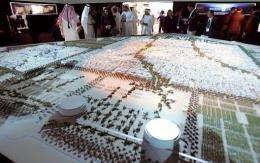 Visitors look at the project model of Masdar City in 2008