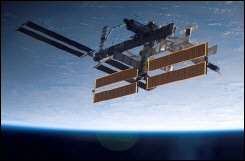 The International Space Station is seen over a blue and white Earth