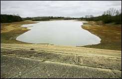 The wall of a reservoir lies exposed due to a low-water levels at Bewl Water
