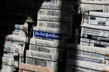 Newspapers are displayed at a newsstand