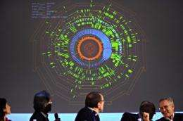 Scientists react as they stand in front of a screen at CERN