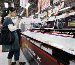 A Japanese customer compares computers at an electronics shop