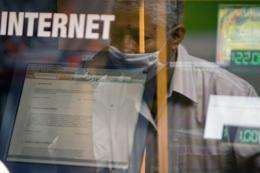 A man looks through the window of an internet cafe at a bus terminal in Mexico City