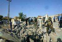 Iraqi police and army survey a destroyed home following a car bomb