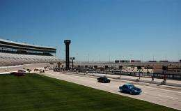 Local area drivers drag race down pit lane at a motor speeedway in Fort Worth