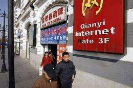 People pass an internet cafe in Beijing