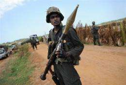 Sri Lankan soldiers stand guard two kilometers from the front line on Puthukkudiyiruppu
