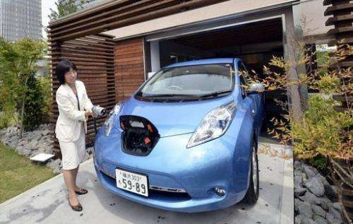A Nissan employee demonstrates the Leaf car