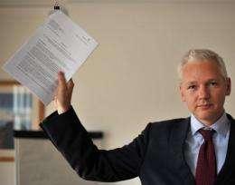 Wikileaks founder Julian Assange holds a legal document