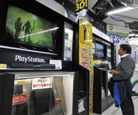 A customer watches a monitor of Sony's videogame PlayStation 3 at a Tokyo electric shop