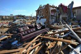 A sofa is seen next to a collapsed house in a tornado stricken neighbourhood