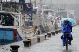 A Taiwanese fish worker rides past the Nanfangauo harbor as typhoon Songda approaches