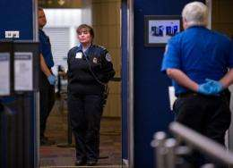 A TSA agent keeps an eye on travelers moving through security lines