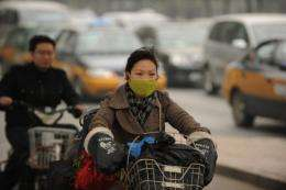 A woman wears a mask as she rides a bicycle in Beijing