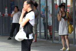 Chinese shoppers chat on their cellphones outside a mall in Beijing