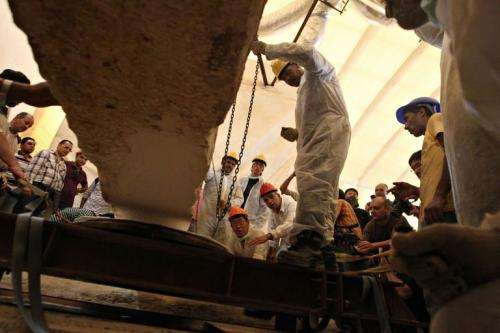 """Egyptian workers remove a rock from the burial site of the second """"Sun Ship"""" for King Khufu"""