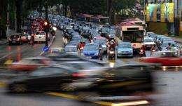 Evening traffic passes through downtown Kuala Lumpur