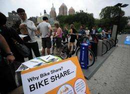 New York residents look at a demonstration of a new bicycle sharing system which will start next year in New York