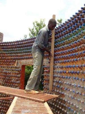 Nineteen-year old mason, Yahaya Musa, checks a wall of made of sand-filled plastic bottles