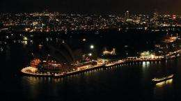 """The lights around Sydney's Harbour and the iconic Opera House (L) turned off to mark """"Earth Hour"""""""