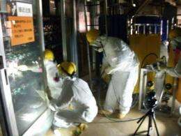 Workers adjusting meters of temporary facilities at the second reactor at TEPCO's Fukushima Dai-ichi nuclear power plant