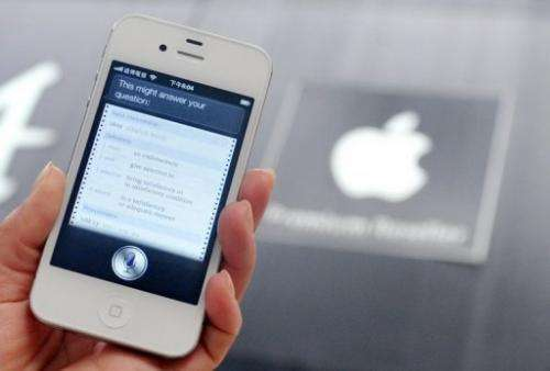 """A woman displays """"Siri"""", voice-activated assistant technology, on an Apple iPhone 4S in Taipei"""