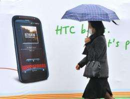 A woman walks past a billboard displaying a handset of Taiwan smartphone maker HTC in Taipei