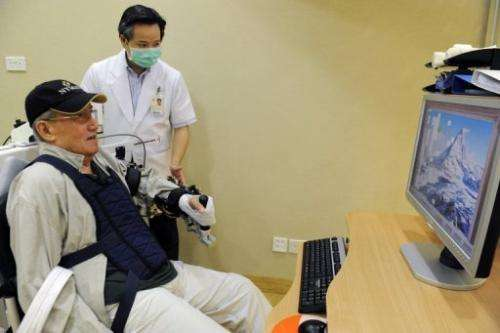 An elderly patient trains his hand-eye coordination by using the Armeo robotic arm