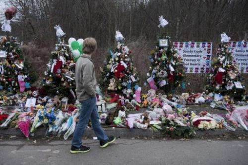 A boy walks along a makeshift memorial near Sandy Hook Elementary School on December 20, 2012 in Newtown, Connecticut