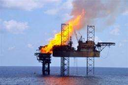 A fire on the West Atlas drilling rig (R) and the Montara wellhead platform in 2009