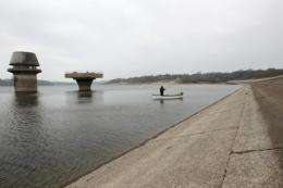 A fisherman stands on his boat on the water of the half-full Bewl water reservoir in Kent in early April