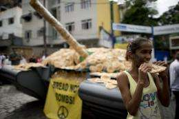 A girl eats bread next to a fake tank covered with bread -- a protest against the weapons market