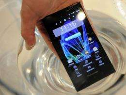 A man places a Panasonic Eluga Power waterproof smartphone in a glass of water