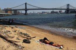 A man relaxes on a small beach along the East River in New York City