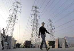 A man walks beneath power lines in Beijing
