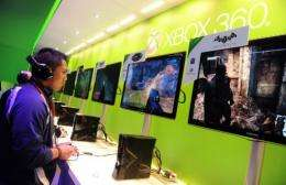 A visitor is seen sampling games on the XBOX 360 at an electronics show in Las Vegas