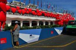 A worker waters the plants in front of the red carpet of the 69th Venice film festival