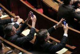 French MPs take pictures with their mobile phones at the National Assembly in March
