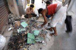 Indian youths dismantle reusable parts from electronic waste on a pavement in 2005