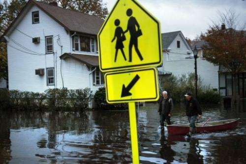 Two men walk with a canoe along the flooded Main Street in Little Ferry, New Jersey.