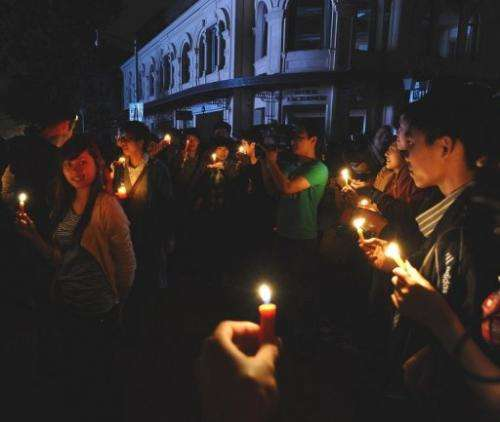 Young people light up candles in the square outside Hanoi Opera House to mark the sixth global Earth Hour in Hanoi