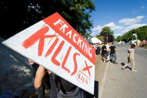 """An anti-fracking protester holds a """"Fracking kills"""" poster outside a test drill site in Balcombe on August 20, 2013"""