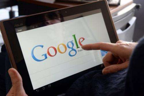 A woman chooses the Google web search engine front page on her tablet in the French western city of Rennes, May 13, 2013