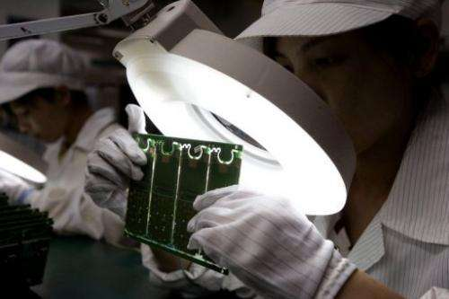 Chinese workers make mobile handsets at a factory in Shenzhen on December 19, 2008