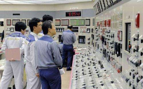 Kansai Electric Power Co engineers check readings at the Oi nuclear power plant, Fukui prefecture, July 19, 2012